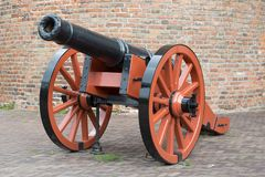 Old medieval artillery canon before a brick wall Stock Photo