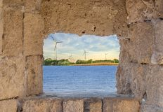 Old medieval castle frame window with wind turbine offshore royalty free stock image