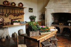 Old medieval kitchen copper pans fireplace table chairs. Vegetables stock photography