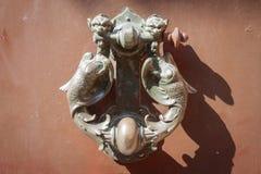 Old medieval metal handles on dark wooden door Stock Photography