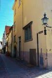 Old medieval Narrow Street in Tallinn with a lantern on the wall, Estonia Stock Photos