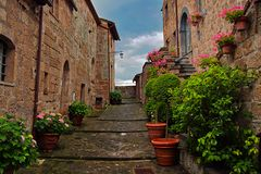 Old ancient stairs in romantic town Civita in Italy with red flowers royalty free stock photos