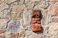 Old medieval stone wall with face of baccus, god of winery. Old medieval stone wall with face of baccus, the god of winery royalty free stock images