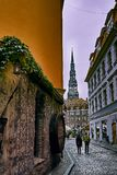 Old medieval street at night with Saint Peters Lutheran church in Riga, Latvia on the background. Old medieval street at night with Saint Peters Lutheran church Royalty Free Stock Photography