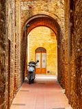 Old medieval street of San Gimignano with small motorcycle, Tuscany, Italia Royalty Free Stock Image