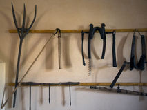 Old medieval tool. Historical farm house foundation, saw, vice, axe, hoe, flail, pitch fork, drill. Royalty Free Stock Photos