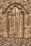 Old Medieval Wooden Door With Decorative Arch And Autumn Leaves. HDR Shallow Depth of Field Sepia Tone Royalty Free Stock Photo