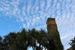 Old Mediterranean chimney with palm trees and blue sky in the background stock photography