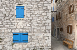 Old mediterranean city. Typical mediterranean city with narrow streets and stone houses with colorful windows Royalty Free Stock Photography