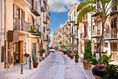 Old mediterranean steet with tourist in Cefalu, medieval city of. CEFALU, SICILY - SEPTEMBRE 16,2014: Old mediterranean steet with tourist in Cefalu, medieval Stock Image