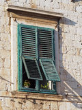 Old mediterranean window with green shutters Royalty Free Stock Image