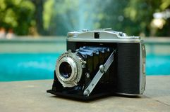 Old medium format camera. An old medium format camera in the edge of garden fountain in Lublin Stock Image