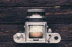 Old medium format film camera art deco style. Old silver analog medium format film camera art deco style with waist level viewfinder on old wooden backdrop Royalty Free Stock Image