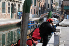 Old Meets New. What appears to be a classic Italian scene -- a gondolier in Venice, Italy -- is updated, as the gondolier is talking on a cel phone royalty free stock photos