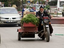 Old meets new on the streets of Turkish city. Grocer transporting his vegetables to bazaar market. Stock Photos
