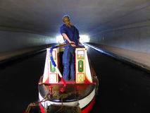 Narrowboat passing under bridge Stock Images