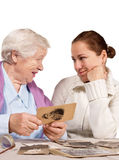 Old memories. Old mother and her adult daughter sitting together and looking at very old photo stock images
