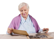 Old memories. Aged woman looking at very old photographs Royalty Free Stock Image