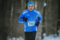 Old men athlete runs at winter Park Stock Image
