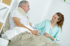 Old man in bed with nurse touching arm stock photos