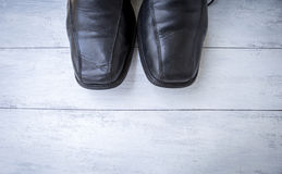 Old men black leather shoes on white wood texture background Stock Photos