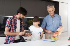 The old man is preparing a salad for Thanksgiving, a man and a boy are watching something on a man`s tablet Stock Photos