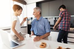While the man is washing dishes, his father and son are drinking tea with cakes Stock Photo