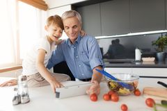 The man hugs his grandson and shows him something interesting on his gray tablet Stock Image
