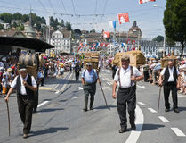 Old men carrying burden. Swiss old man farmers carrying a burden on their back during the jodler's parade in Luzern, Switzerland Stock Image