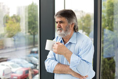Old men with a cup of coffee next to a window Royalty Free Stock Image