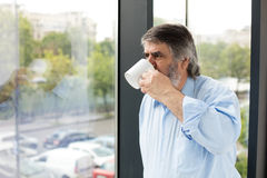 Old men with a cup of coffee next to a window Royalty Free Stock Images