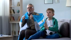 Old man holding Argentina flag, watching football with boy, worrying about game. Old men holding Argentina flag, watching football with boy, worrying about game royalty free stock photo