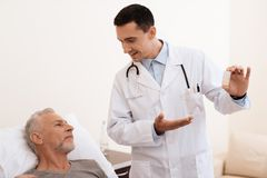 The old man lies on a cot in the medical ward, and next to him stands a doctor. He explains something to the old man. The old men lies on a cot in the medical Stock Images