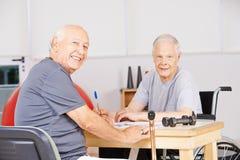 Old men in nursing home solving crossword puzzle Stock Images