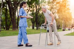 A nurse is standing in the park, next to the old man who goes to her with the help of walkers for adults Stock Photography