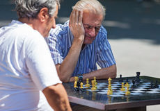 Old men playing chess. BELGRADE, SERBIA - AUG 15: Old men playing chess on  the street on August 15, 2012 in Belgrade, Serbia. City has plan to put chessboards Stock Photography