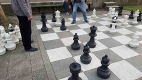 Old men playing giant chess. Old people outdoors in a park playing chess Royalty Free Stock Photos