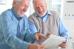 Old men reading a newspaper Stock Photos
