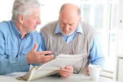 Old men reading a newspaper. At a table royalty free stock photography