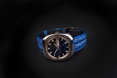 Old men's classic watch with blue strap on black Royalty Free Stock Images
