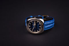 Old men's classic watch with blue strap on black Stock Photos