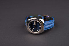 Old men's classic watch with blue strap on black background.  Royalty Free Stock Images