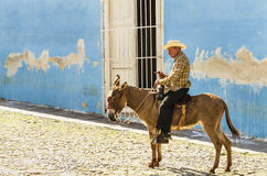 Old men sits on a donkey on the cobblestone street of Trinidad in Cuba and asks turists for money. Purple and white classic American car and blue colonial Stock Photography