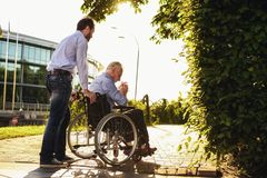 The old man is sitting in a wheelchair in the park. Behind him stands his son. They`re walking. The old man is sad. The old men is sitting in a wheelchair in the royalty free stock photography