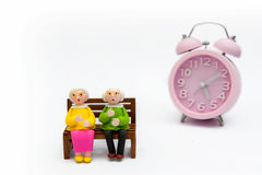 Old men and women with alarm clocks stock photography