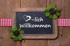 Old menu board with welcome message in german - clovers and ribb Royalty Free Stock Photos