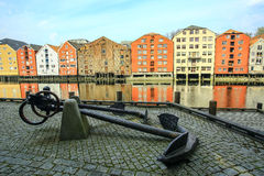 Old metal anchor and historic buildings in Trondheim, Norway Royalty Free Stock Photos