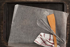 Old metal baking pan with paper and kitchen utensils Royalty Free Stock Image