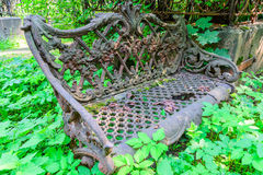 Old metal bench. Abandoned bench, overgrown with grass. Beautiful carved bench with pictures and patterns royalty free stock photos