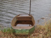 Old metal boat on the shore of the pond Stock Image